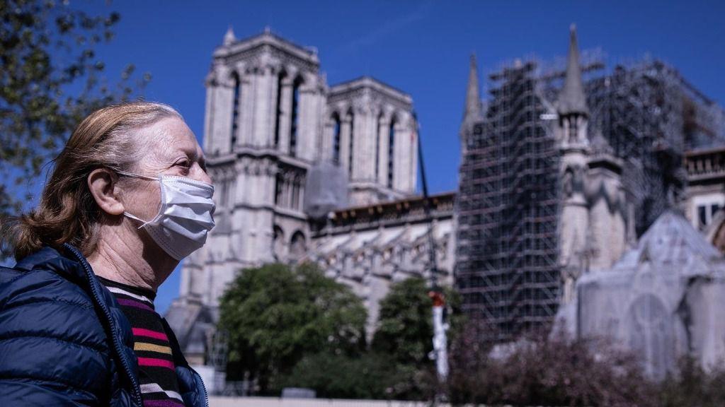 Una mujer con mascarilla pasa por delante de Notre Dame coronavirus francia