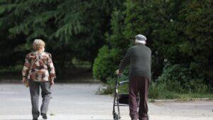 Una mujer y un hombre de edad avanzada pasen por la calle