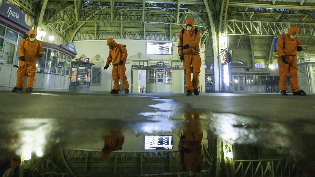 Trabajadores del Ministerio de Emergencias desinfectando una estación de trenes en San Petersburgo