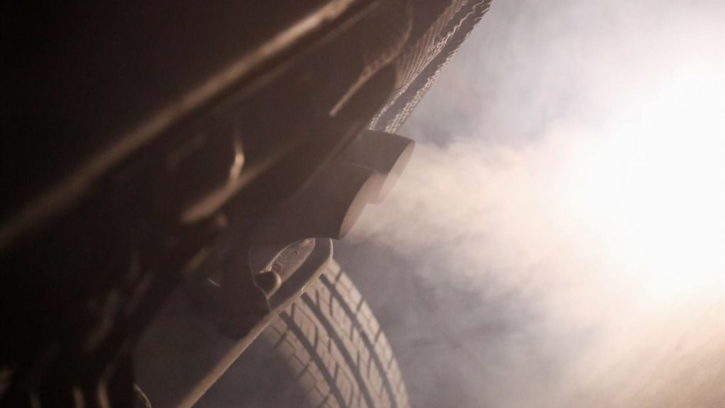 Tubo de escape de un coche emitiendo polución