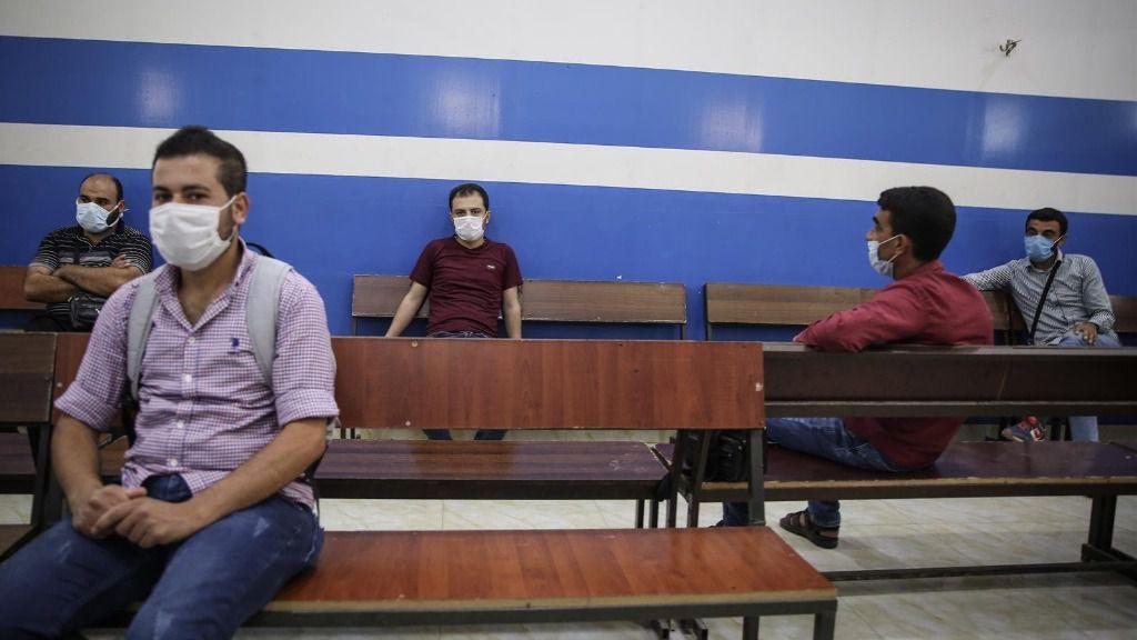 Ciudadanos sirios con mascarillas esperando en el paso fronterizo con Turquía en Bab al Hawa