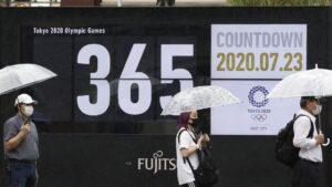 Personas con mascarilla en un paseo que muestra la cuenta atrás para los Juegos Olímpicos de Tokio