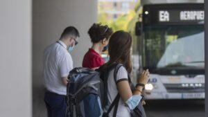 Varias personas en la parada del bus exprés hacia el aeropuerto.