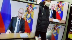 Un ciudadano en una tienda durante la retransmisión de un discurso del presidente Putin