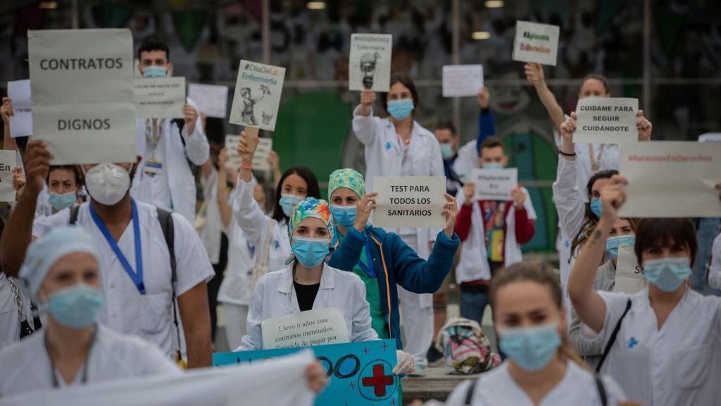 Decenas de miembros del personal sanitario protegidos con mascarilla sostienen carteles durante la concentración de sanitarios en el Día Internacional de la Enfermería a las puertas del Hospital Vall d'Hebron, en Barcelona