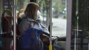 Una mujer con mascarilla en un autobús urbano