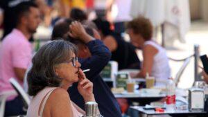 Personas fumando en terrazas y vías públicas durante el día en el que se ha decretado la prohibición de fumar en espacios públicos