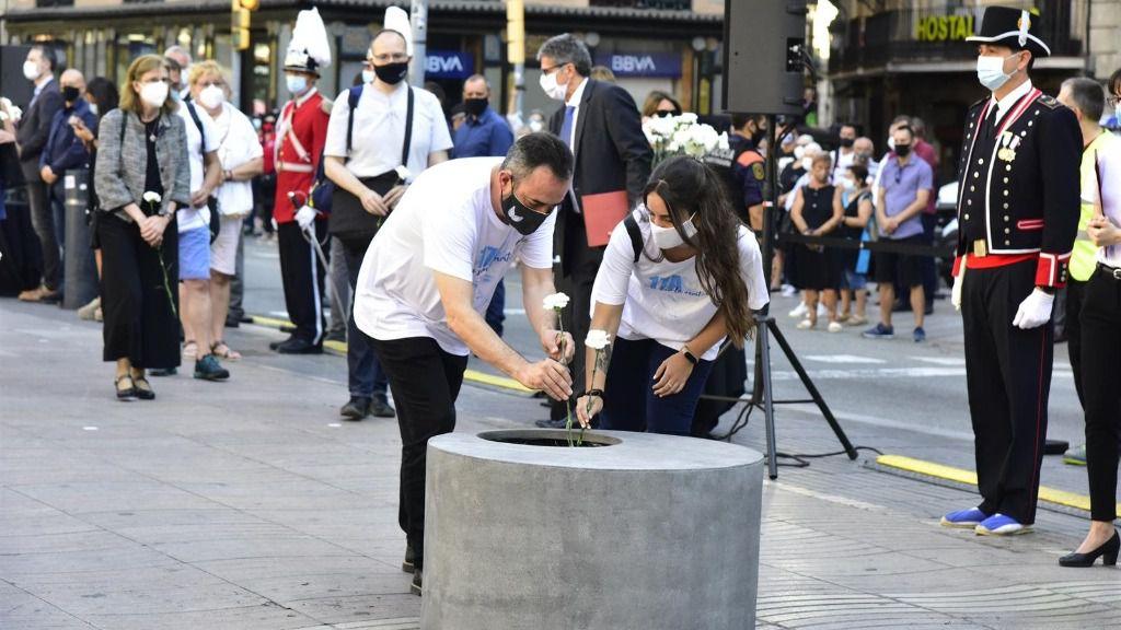 Asistentes dejan rosas blancas y carteles en recuerdo a las 16 personas fallecidas el 17 de agosto de 2017 y a los más de 150 heridos en los atentados de Barcelona y Cambrils durante el homenaje y minuto de silencio celebrado en Las Ramblas