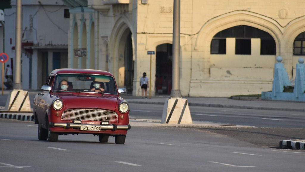 Personas con mascarillas en un coche por las calles de La Habana