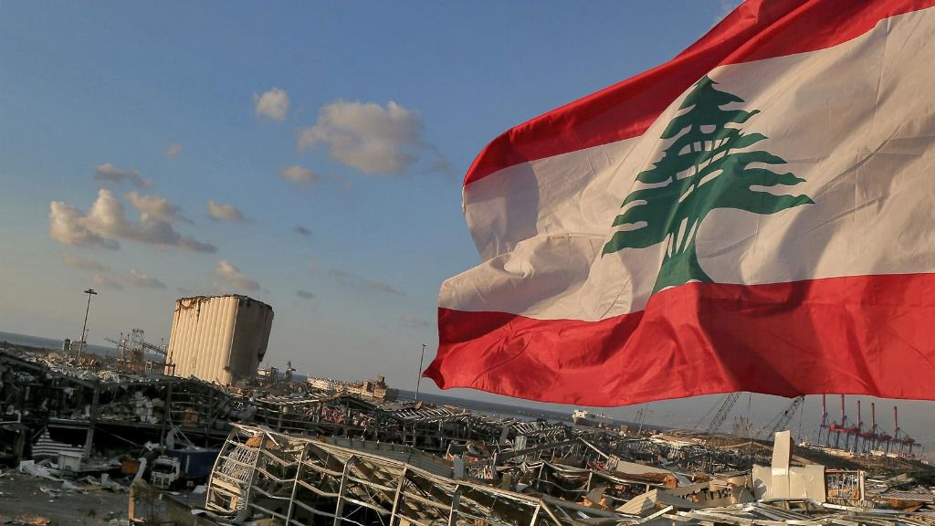 Una bandera de Líbano ondea junto a la zona destruida por la explosión en Beirut
