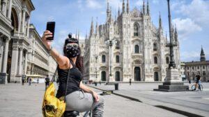 Una mujer con mascarilla se hace un selfie frente a la catedral de Milán
