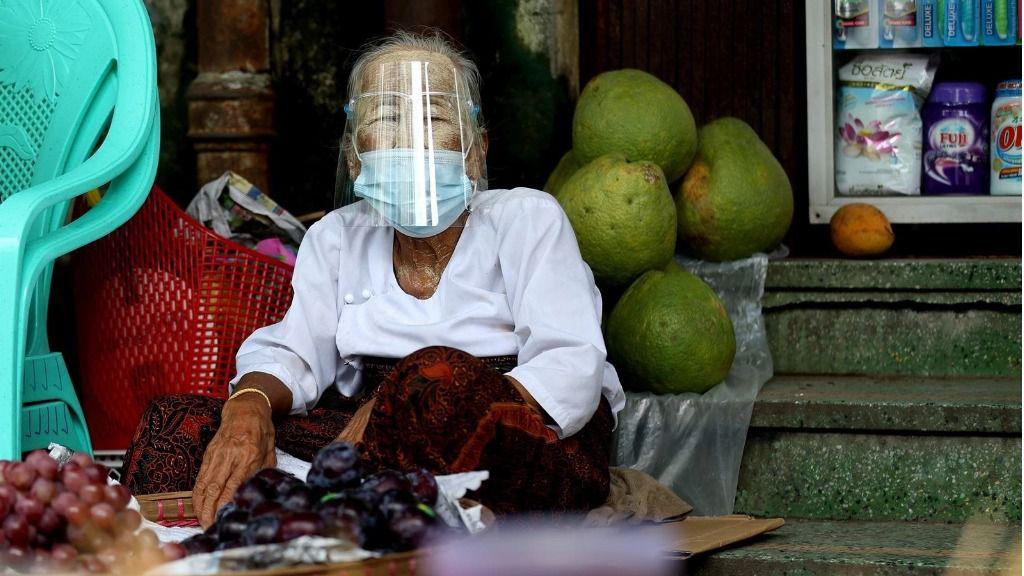 Una mujer con mascarilla en un mercado de Rangún