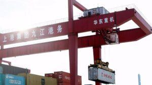 Imagen de una grupo portando un contenedor en un puerto en China.