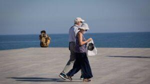Dos personas protegidas con mascarillas pasean por el Paseo Marítimo de la Playa de la Barceloneta, en Barcelona/Catalunya