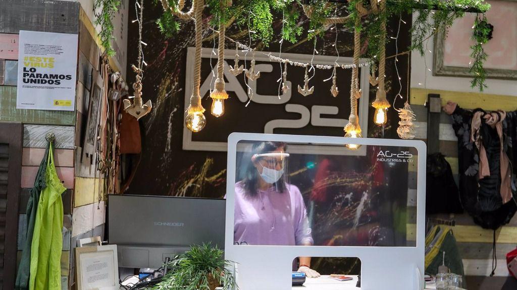 Una mujer protegida con mascarilla trabaja en la tienda AG 25, abierta después de que el Ministerio de Sanidad autorizara a su apertua