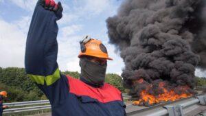Un trabajador de Alcoa San Cibrao levanta el puño durante una manifestación en la que han cortado la Autopista A6 con la quema de neumáticos