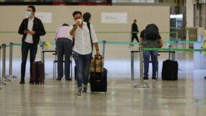 Pasajeros procedentes de Londres rellenan un formulario a su llegada a Barajas