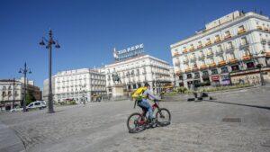 Un 'rider' de Glovo circula por la Puerta del Sol el día, en Madrid