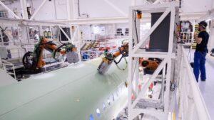 Un empleado de Airbus observa el trabajo de dos robots en el fuselaje de un modelo A320 en la planta de la empresa en Finkenwerder, al sur de Hamburgo