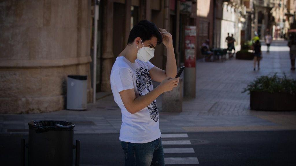 Un joven protegido con mascarilla camina por una calle del centro de Lleida, capital de la comarca del Segrià, en Lleida, Catalunya
