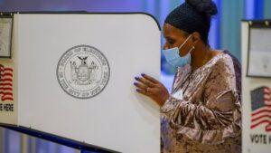 Una mujer con mascarilla vota en Nueva York