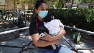 Lucía, una mujer con su bebé en brazos, acude a las puertas de la Parroquia Santa María Micaela para recibir una ayuda alimentaria. En Madrid (España), a 29 de mayo de 2020.