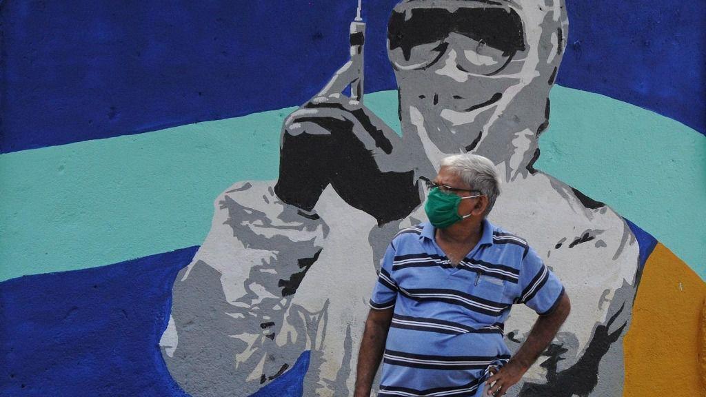 Un hombre con mascarilla ante un mural de un trabajador médico en Bombay coronavirus india