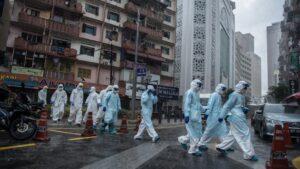 Trabajadores del Ministerio de Sanidad saliendo de un edifcio de Johannesburgo tras hacer pruebas de coronavirus a los vecinos