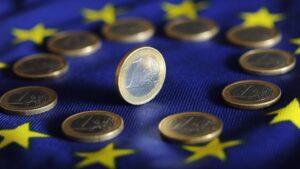 Monedas de euro sobre la bandera de la UE