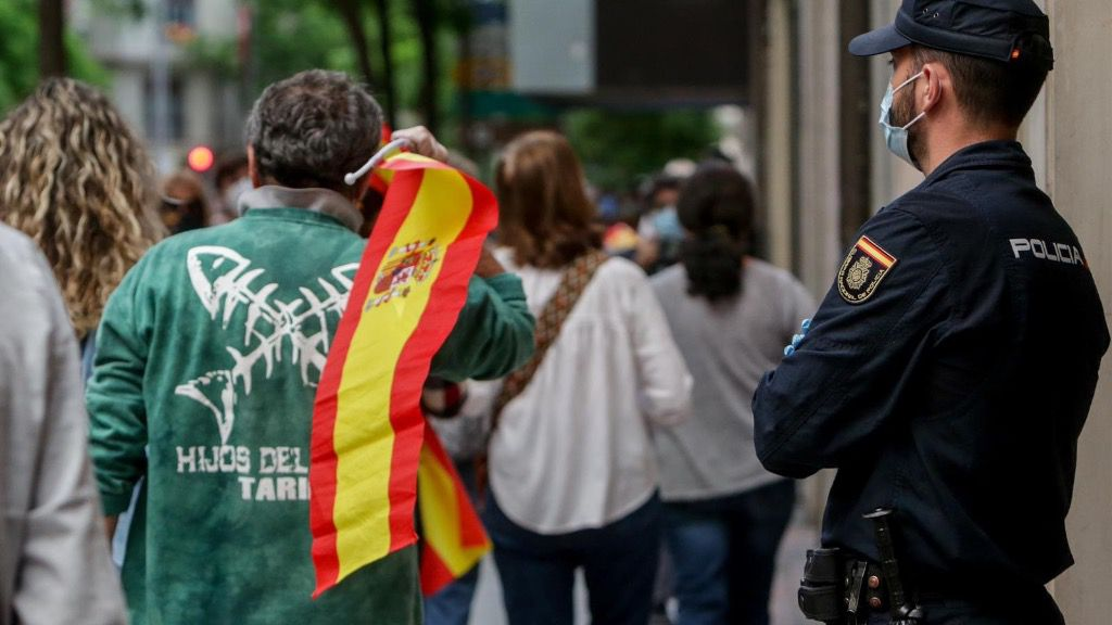 Un hombre con una bandera de España durante el cuarto día de protestas por la gestión del Gobierno en la crisis del coronavirus, frente a la sede del PSOE de la calle Ferraz en Madrid a 19 de mayo de 2020