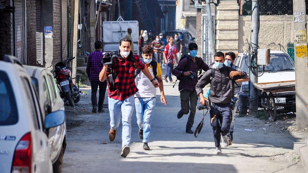 Un grupo de periodistas corre durante los enfrentamientos que tuvieron lugar en unas recientes manifestaciones en Cachemira por la muerte de tres personasa a manos de las autoridades de India