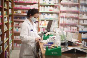 Una farmacéutica con mascarilla despacha medicamentos