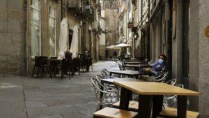 Una mujer permanece sentada en una terraza del barrio de O Coutoen Ourense