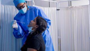 Un trabajador sanitario protegido le realiza a una mujer un test PCR en el Centro de Especialidades Carabanchel Alto.
