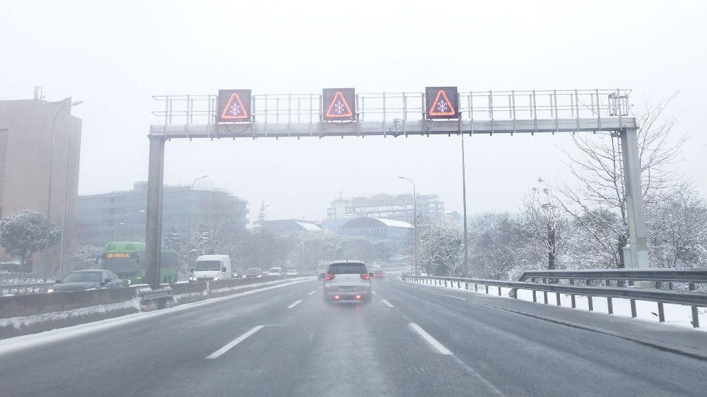 Anuncio de precaución por nieve en una carretera de la capital en el segundo día de nieve tras el paso de la borrasca Filomena