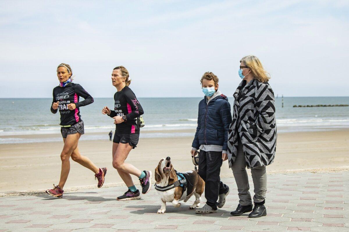 Dos mujeres corren por la playa mientras que una mujer y un niño pasean un perro en una imagen de archivo de las playas de Dunkerque