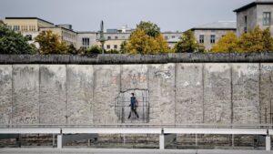 Un hombre con mascarilla pasando ante un muro de un museo en Niederkirchnerstrasse, en Berlín alemania coronavirus