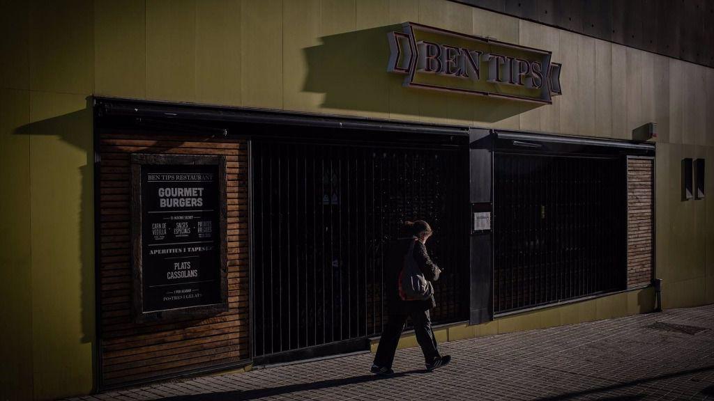 Un hombre pasa por un bar cerrado en Barcelona.