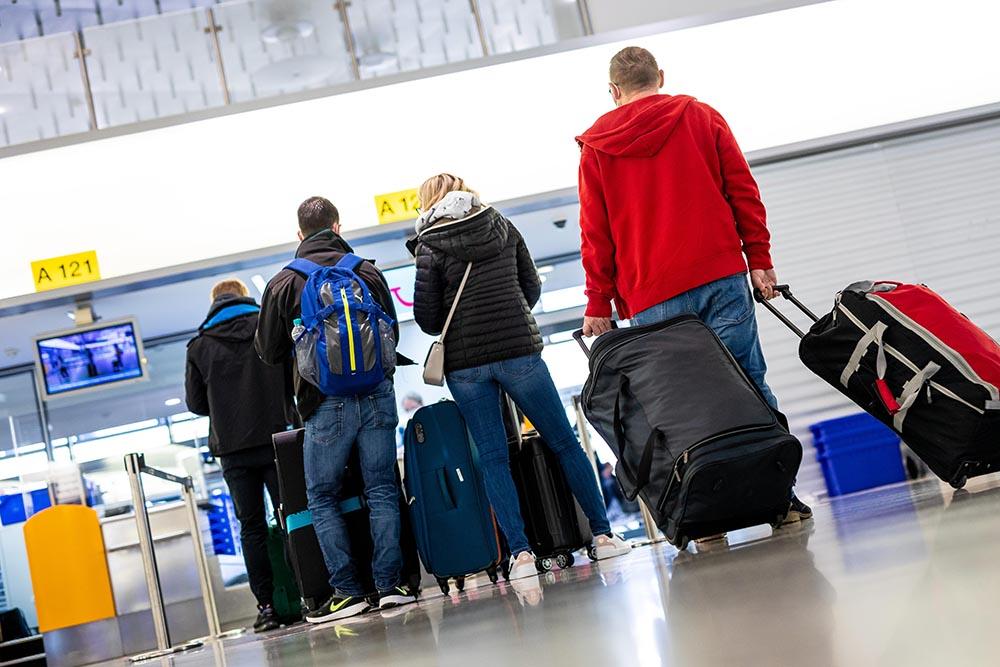 Pasajeros en el aeropuerto de Hanover aguardan su turno para embarcar rumbo a la popular isla española de Mallorca. Foto: Moritz Frankenberg/dpa