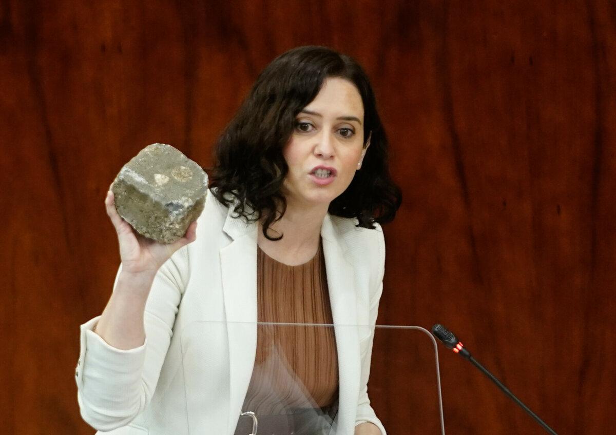 Isabel Díaz Ayuso muestra un adoquín en la Asamblea.