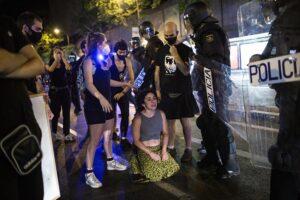 Una joven arrodillada frente a antidisturbios de la Policía Nacional en el barrio de Argüelles