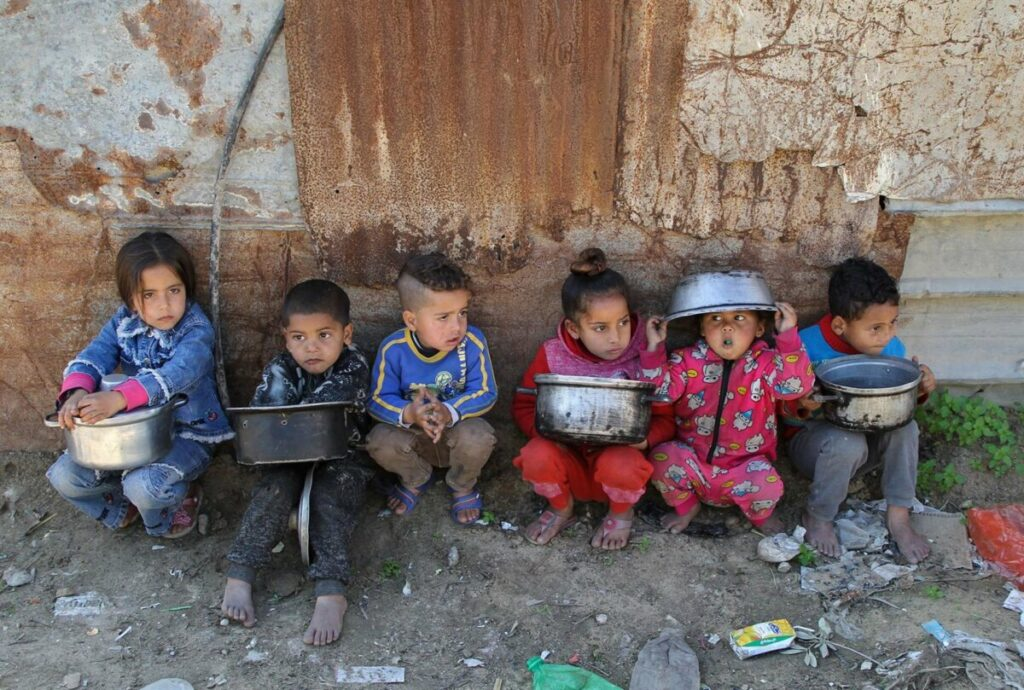 Niños palestinos esperan para recibir comidas benéficas en el barrio de Al Zaitún, en el este de la ciudad de Gaza - RIZEK ABDELJAWAD / XINHUA NEWS / CONTACTOPHOTO