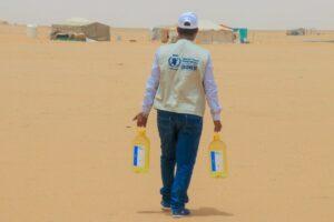 Un trabajador lleva botellas de aceite vegetal del PMA para distribuirlas entre los desplazados internos en un campamento de Yemen - PMA / HANI SALEH