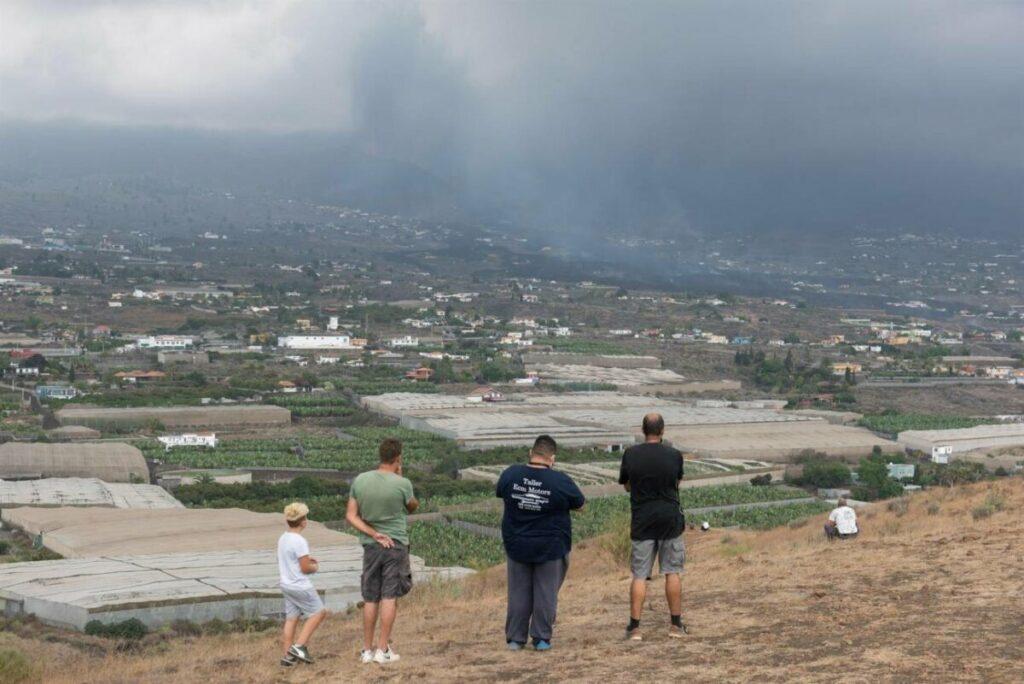 Cuatro vecinos observan desde un alto el avance de la colada de lava del volcán de La Palma en las cercanías de la localidad de La Laguna. EFE / Carlos de Saa